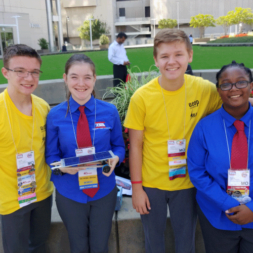 An image of all 4 students who participated in the conference holding up their solar car they built