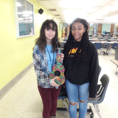 An image of two students standing side by side holding an instrument they made out of recyclables.
