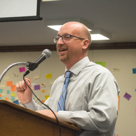 An image of Dr. Croley, principal at McCluer North High School, speaking at a podium.