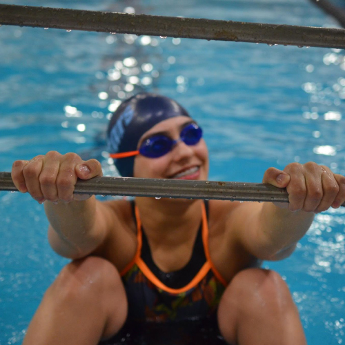 An image of Madison holding on to a rail in the pool.