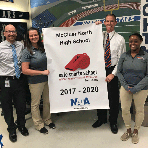 An image of athletics director Chris K., principal Dr. Croley, and 2 reps from NATA with banner.