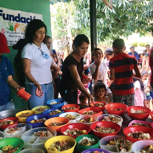 An image of adults and volunteers serving food to children in Venezuela.