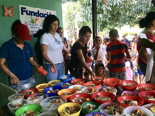 An image of adults and volunteers serving food to children in Venezuela