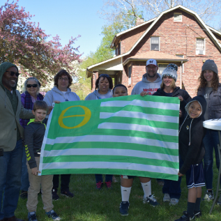 Adults and students holding ecology flag